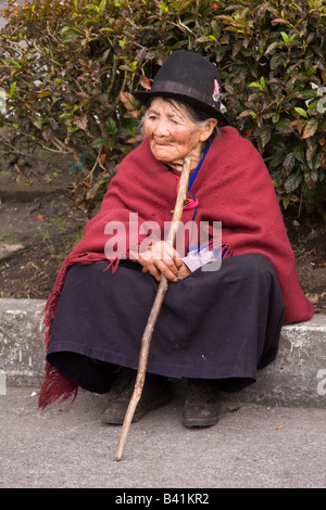 Elderly Quechuan woman wearing traditional dress with a walking stick sitting on a curb in Banos Ecuador - Stock Photo