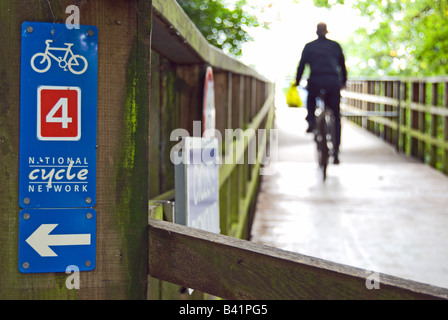 male cyclist in silhouette on teddington bridge, crossing the river thames, close to a national cycle network sign - Stock Photo