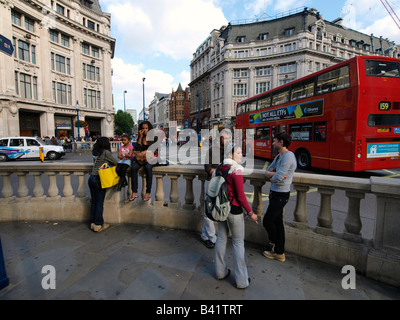 Shoppers resting at Oxford Circus London United Kingdom - Stock Photo