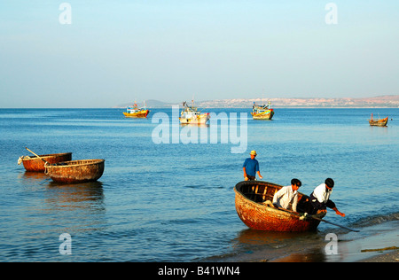 Traditional basket boats and fishing ships in the fishing port of Mui Ne, Viet Nam - Stock Photo
