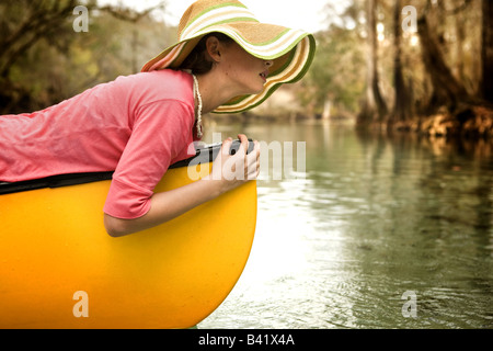 A young girl relaxes on her canoe in the clear water, cypress lined river of a fresh water spring in High Springs, - Stock Photo