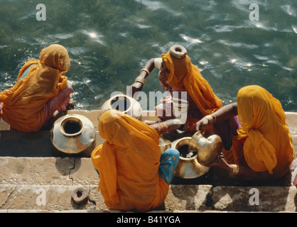 Women collecting water from Gadisar lake, Jaisalmer, Rajasthan, India - Stock Photo