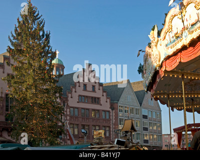 christmas tree with fairy lights and a merry go round on the square Roemer Römer Römerberg city hall in Frankfurt - Stock Photo