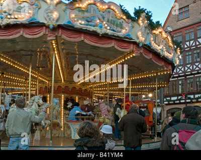 Christmas fair with merry go round with light for children on the move parents looking square Roemer Römer Römerberg - Stock Photo
