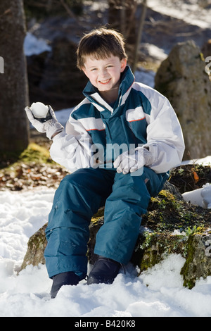 Portrait of a boy holding a snowball, sitting on a tree stump He is wearing a white and blue ski outfit outside - Stock Photo