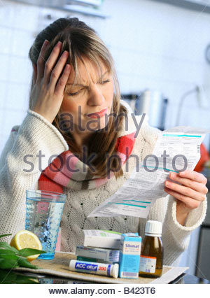 woman with influenza and sore throat taking some medicine, reading package informations - Stock Photo