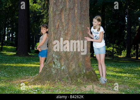 Two young girls playing hide and seek in a forest area - Stock Photo