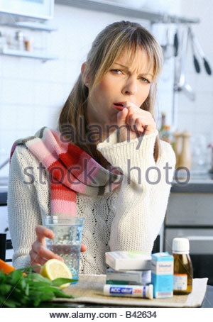 woman with influenza and sore throat taking some medicine - Stock Photo