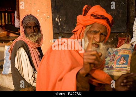 An aged man with a beard sits on a wall in the city of Varanasi, India. A sadhu wearing red sits in the foreground. - Stock Photo