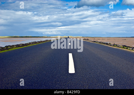 A long straight road stretching out on the Holy Island causeway Northumberland Great Britain UK 2008