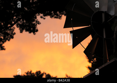 Sharp metal corners of a decorative windmill's blades silhouetted against bright orange sky. - Stock Photo
