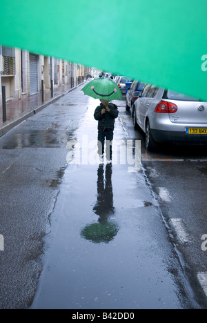 a small boy walks towards camera with green umbrella in the rain - Stock Photo