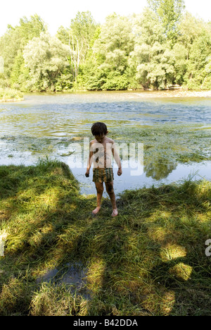 a young boy stands on a river bank looking down athis stomach covered in river mud and weed - Stock Photo