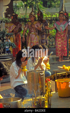 Young Thai women kneeling in prayer with Thai classical dancers performing behind at Erawan Shrine, city centre, - Stock Photo