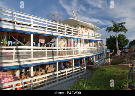 A public ferry moored and unloading goods or passengers at one of the stops along the Madeira river heading towards - Stock Photo