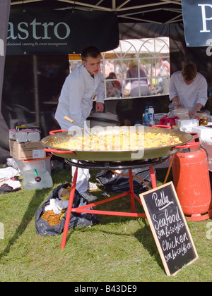 A young male chef cooking Paella in a large skillet outdoors at a village fete. - Stock Photo