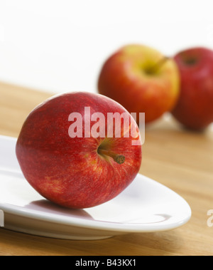 FRESH RED APPLES ON WHITE PLATE AND WOODEN KITCHEN TABLE - Stock Photo