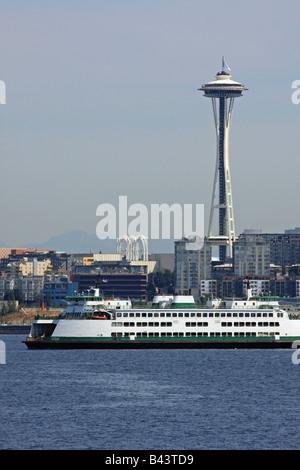 With a Washington State Ferry passing in the foreground, the Space Needle rises above the Queen Anne area skyline - Stock Photo