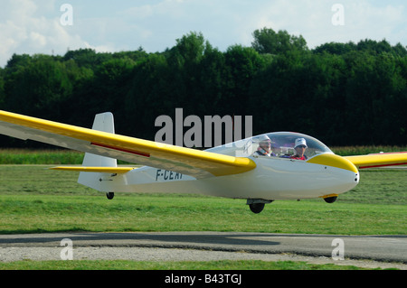 A trainer glider ASK-13 landing on runway airfield - France - Stock Photo