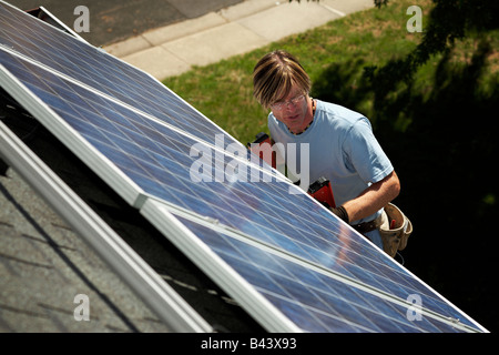 A man installing an array of solar panels on the roof of his home. - Stock Photo