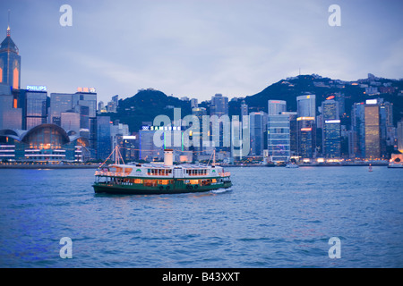 China Hong Kong Skyline viewed from Kowloon at dusk with star ferry - Stock Photo