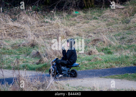 boy on mini motorbike in a country park during school hours smoking, and wearing a hoodie - Stock Photo