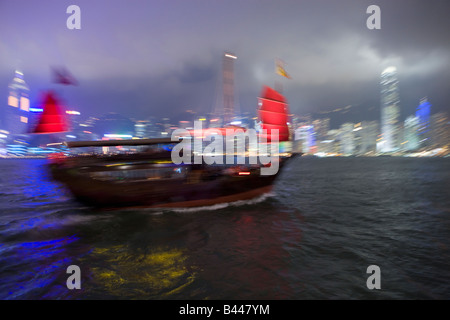 China Hong Kong Skyline and Chinese Junk viewed from Kowloon at dusk - Stock Photo
