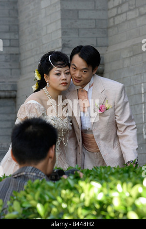 Photographer taking pictures of a bridal couple, Beijing, China - Stock Photo