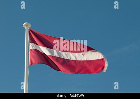 Latvian flag white stripe on red background against blue sky - Stock Photo