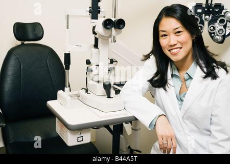 Asian female optometrist in office - Stock Photo