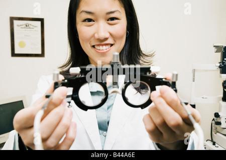 Asian female optometrist holding equipment - Stock Photo