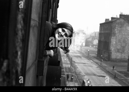 A youth worker pops her head out of one of the windows in a housing slums in the Gorbals district of Glasgow January - Stock Photo