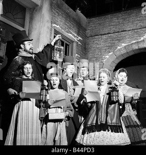 Dress rehearsal of ITV Merry Christmas a musical version of Dicken s Christmas Carol The carol singers with Forbes - Stock Photo