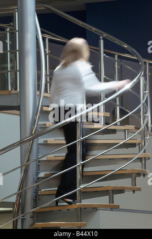 Woman climbing a stainless steel spiral staircase in a modern open plan office