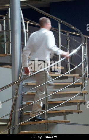 Man climbing a stainless steel spiral staircase in a modern open plan office