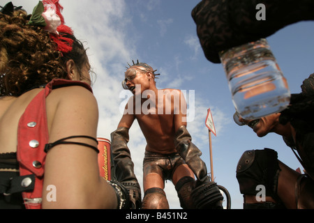 Performance artists dressed and acting as giant insects move through the crowd in the One World Sage area - Stock Photo