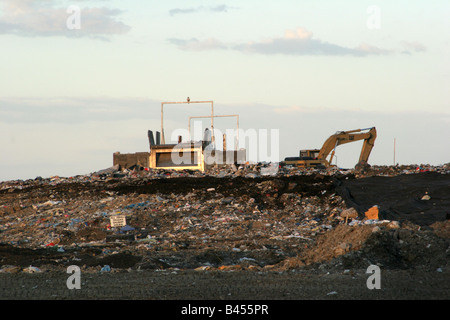 A landfill for garbage in Wisconsin Hawk on top of the machinery Small trucks dump here Sign - Stock Photo
