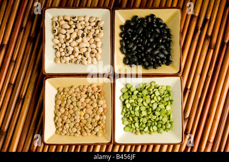 four dishes with lentils, black beans, split peas, black eyed peas. - Stock Photo