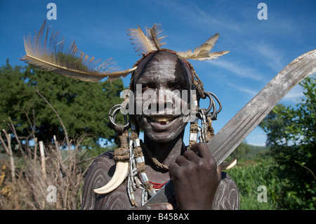 A man from the Mursi tribe holds a machete, Mago National Park, Southern Ethiopia, East Africa - Stock Photo