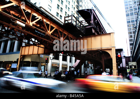 CARS PASSING AND PEOPLE CROSSING WELLST STREET UNDER EL TRAIN IN DOWNTOWN CHICAGO ILLINOIS USA DURING AFTERNOON - Stock Photo