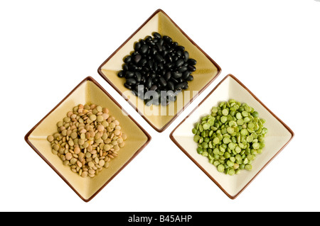 three plates with lentils, black beans, split peas - Stock Photo