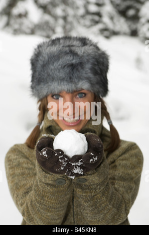 Austria, Salzburger Land, Altenmarkt, Young woman presenting snowball - Stock Photo