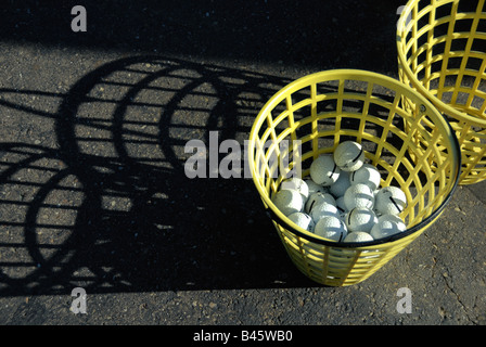 A bucket of golf balls at a golf driving range casts interesting shadows in the midday sun. - Stock Photo