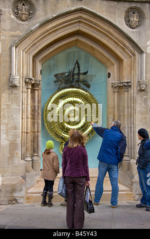 Passers bye discussing the new Corpus Clock, showpiece of Corpus Christi's new library - Stock Photo