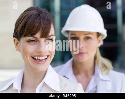 Germany, Baden-Württemberg, Stuttgart, Two businesswomen, one wearing hard hat, portrait - Stock Photo