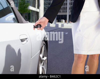 Germany, Baden-Württemberg, Stuttgart, Female person at sports car using remote control key, low section view - Stock Photo
