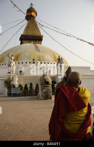Buddhist monk praying in front of the great stupa of Boudha Nepal - Stock Photo