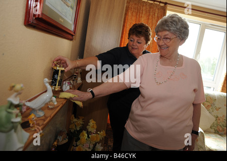Council Homecare Staff help an elderly lady to dust and clean her home through support and help - Stock Photo