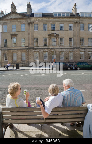 People having a tea picnic on bench in street Bath UK - Stock Photo
