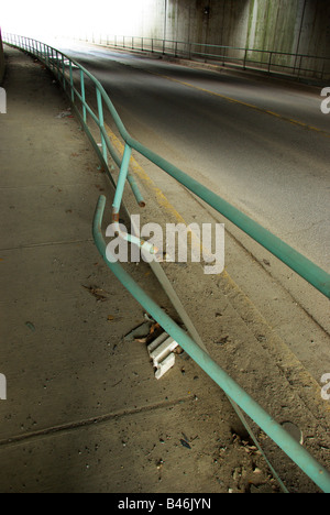 Damage to a railing on a pedestrian area under a railroad bridge from a car accident - Stock Photo